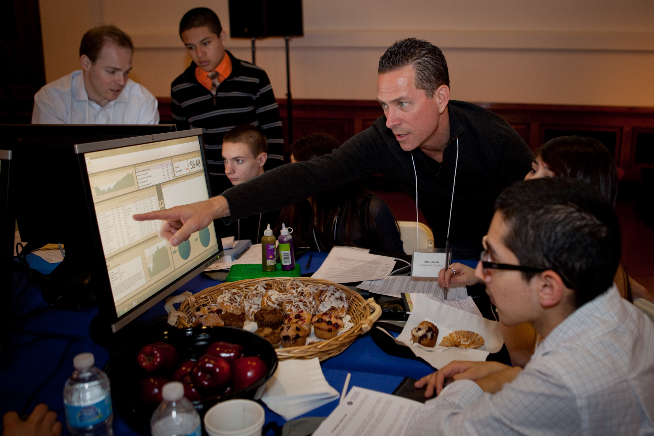 Alec Litowitz, founder and CEO of Magnetar Capital, works with students during the Magnetar Ultimate Stock Trading Challenge. Nearly 100 Chicago high school students took part in the competition, which raised $9,000 for Chicago public high schools. (Photo: Business Wire)