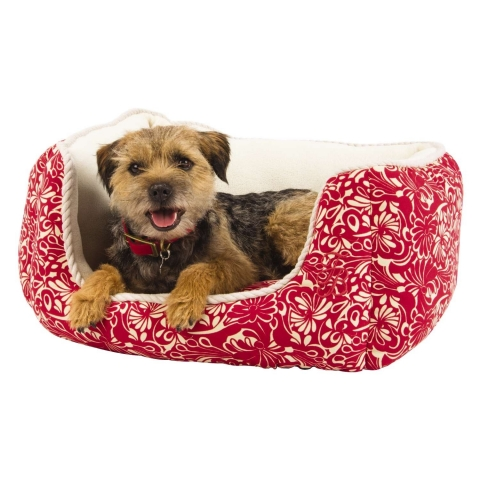 Nestled under a palm tree in the warm sun, the Tommy Bahama Pets floral cuddler bed from PetSmart is ...