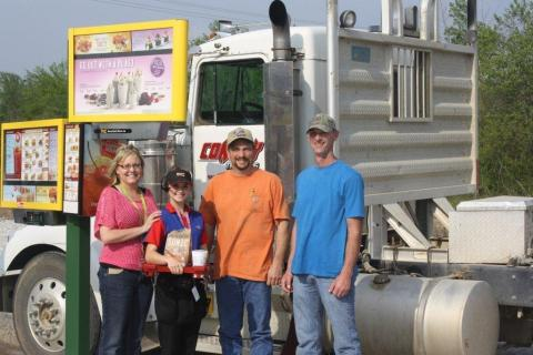 Valliant, Okla., SONIC owners, Julie Dorries (far left) and Tommy Dorries (far right), along with Carhop Halee Elledge (second from left), greet a local guest as he pulls into the first SONIC Drive-In stall built specifically for truck drivers. (Photo: Business Wire)