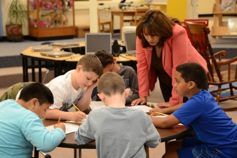 Ximena Cheatham helps students with savings lesson. (Photo: Mattox Photography)