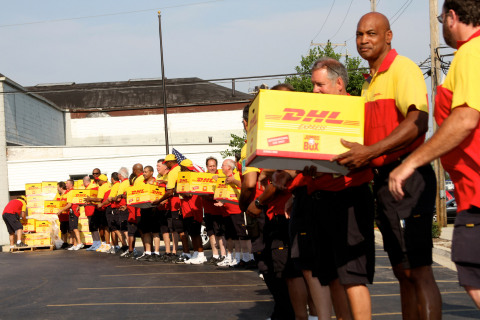 DHL employees load pizzas into trucks at the Guinness Book of World Records' largest pizza delivery in history. (Photo: Business Wire)
