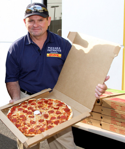 Mark Evans, founder of Pizza 4 Patriots, shows off one of the pizzas that was sent to troops overseas as part of the Guinness Book of World Records' largest pizza delivery in history. (Photo: Business Wire)