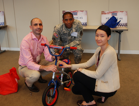 Moody's employees participate in a USO Bike Build event for military families at the company's headq ...