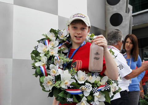 """Christopher Bienusa, a 12-year-old from Alexandria, Minn., celebrates winning the Hot Wheels """"World's Best Driver Championship"""" in traditional Indy 500 fashion on Saturday, May 25 at the Indianapolis Motor Speedway. Coached by racing legends Mario and John Andretti, Smith's toy-size car finished first on the world record-setting one mile-long iconic Hot Wheels orange toy track. (Photo: Business Wire)"""