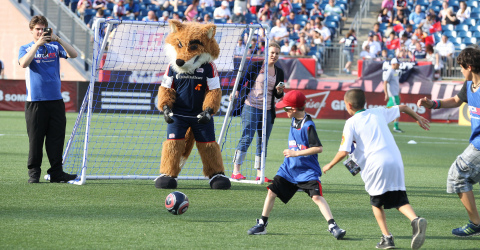New England Revolution mascot Slyde plays goalie in a fans' 4-vs.-4 soccer match during halftime of ...