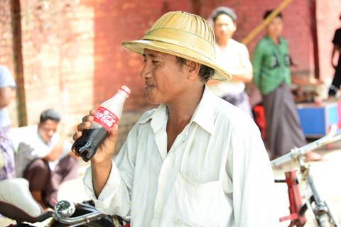 A Myanmar citizen enjoying a Coca-Cola produced in the country for the first time in more than 60 ye ...