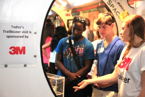 A 3M volunteer shows students from Four Points Middle School an exhibit in the new Trailblazer II fr ...