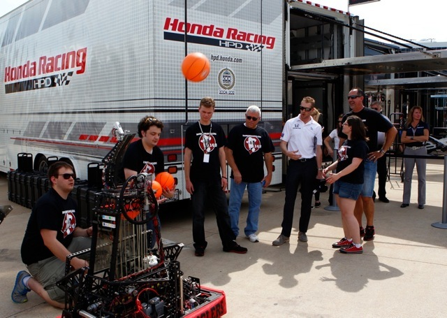 "FIRST(R) Robotics Competition (FRC(R)) Team ""Robowranglers"" from Greenville, Texas demo their basketball-shooting robot for IZOD IndyCar series racer Charlie Kimball at the Firestone 550 at Texas Motor Speedway on June 8, 2013. (Photo: Business Wire)"