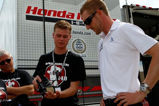 "Student team member from FIRST(R) Robotics Competition (FRC(R)) Team ""Robowranglers"" from Greenville, Texas shows IZOD IndyCar series racer Charlie Kimball the inner-workings of his team's robot at the Firestone 550 at Texas Motor Speedway on June 8, 2013. (Photo: Business Wire)"