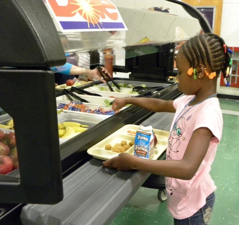 A first grade student at Grandview Elementary School in Piscataway, NJ enjoys the school's new salad bar donated by Dole Food Company. (Photo: Business Wire)