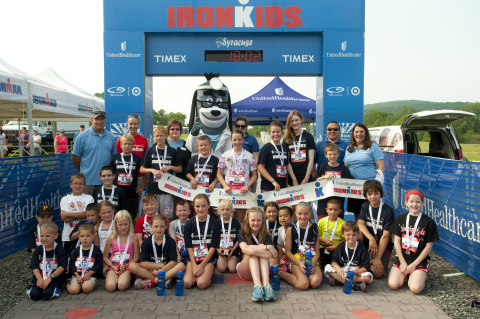 Young athletes are pictured with Linda Goldsworthy, Director, Upstate Market, UnitedHealthcare Community Plan (back row, far right, blue shirt); Susan Healy-Kribs, Senior Community Relations Manager, UnitedHealthcare Community Plan of New York (back row, third from left, blue and black shirt); and UnitedHealthcare mascot Dr. Health E. Hound at the UnitedHealthcare IRONKIDS Syracuse Fun Run. (Photo: Business Wire)