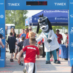 UnitedHealthcare mascot Dr. Health E. Hound is at the finish line as young athletes complete the UnitedHealthcare IRONKIDS Syracuse Fun Run Race. Photo Credit: Rick Mossotti