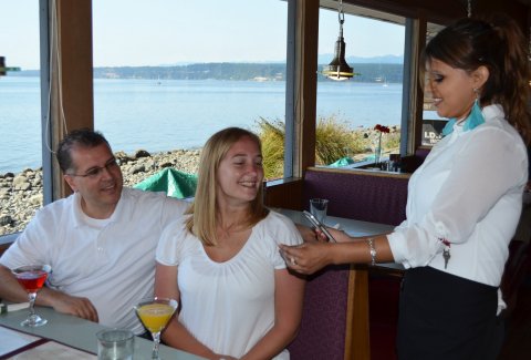 Waitress Peggy Buntin from Bayview Restaurant, in Port Townsend, WA, scans a young couple's ID cards with her cell phone and the barZapp product on Apple's iTunes before serving them alcohol. (Photo: Business Wire)