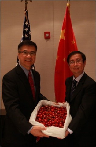 Ambassador Gary Locke (left) and Daniel Zhang (right), president of Tmall.com, receive the first batch of American cherries shipped to China as part of a collaborative sales campaign between the U.S. Department of Agriculture and Tmall.com to offer Chinese consumers with high-quality American food products. (Photo: Business Wire)