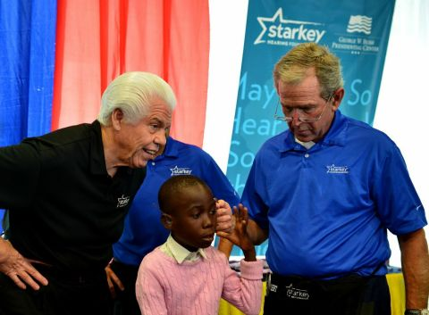 Former President George W. Bush and Bill Austin, founder of the Starkey Hearing Foundation, fit a patient with hearing aids at a mission in Dar es Salaam. (Photo: Starkey Hearing Foundation)