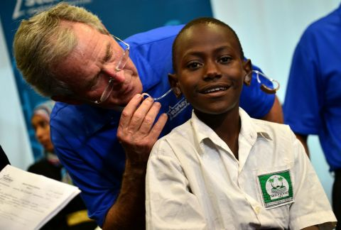 Former President George W. Bush fits a patient with hearing aids at a Starkey Hearing Foundation mission in Dar es Salaam. (Photo: Starkey Hearing Foundation)