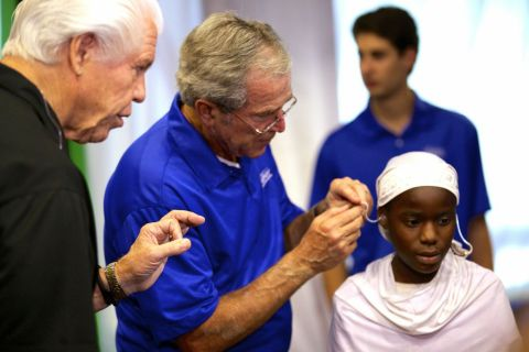 Former President George W. Bush fits a patient with hearing aids at a mission in Dar es Salaam, as Bill Austin, founder of the Starkey Hearing Foundation, looks on. (Photo: Starkey Hearing Foundation)