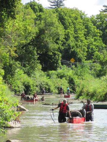 Green Mountain Coffee Roasters, Inc. employees haul tires from the Winooski River during the 2012 an ...