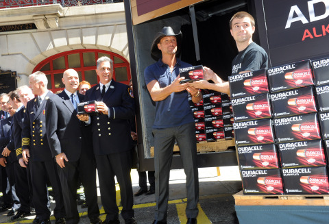 Country music star Tim McGraw, center, hands off new Duracell Quantum batteries to the FDNY to kick ...
