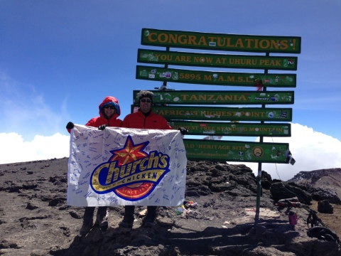Church's Chicken CEO Jim Hyatt and his wife Christa, reach the top of Africa's Mt. Kilimanjaro and proudly display the Church's flag signed by Church's Restaurant Support Team. (Photo: Business Wire)