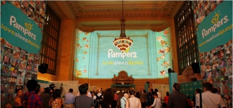 Guests watch as the 3-D photo installation is unveiled at the Pampers