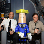 """Ted Striker"" (Robert Hays), ""Roger Murdock"" (Kareem Abdul-Jabbar), and Otto Autopilot in the original Airplane! cockpit to shoot Wisconsin Tourism commercials in Los Angeles on September 19, 2013. (Photo: Business Wire)"