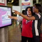Atlanta Falcons fans use interactive technology from Duluth, Ga.-based NCR that helps them navigate their way around the Georgia Dome simply with a tap of a finger. (Photo: Business Wire)