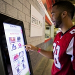 An Atlanta Falcons fan uses self-service technology from Duluth, Ga.-based NCR to select, purchase and pick up merchandise at the Georgia Dome during the game. Fans will spend less time in line and more time in their seats watching the game. (Photo: Business Wire)