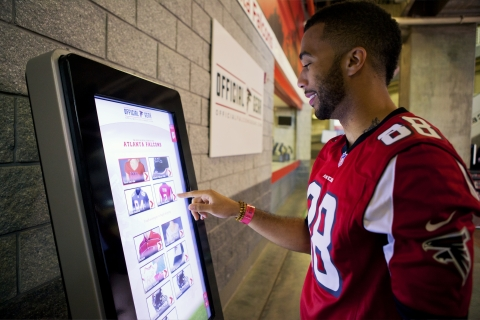 An Atlanta Falcons fan uses self-service technology from Duluth, Ga.-based NCR to select, purchase a ...