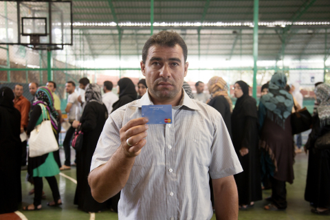 Syrian refugee Ali Ahmad Farhat holds his MasterCard / WFP e-card as others stand in line to receive theirs, at a basketball court. (Photo: Business Wire)