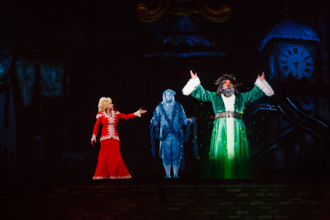Dolly Parton's Ghost of Christmas Past hologram gestures to the hologram of the Ghost of Christmas Present during the curtain call of Dollywood's A Christmas Carol. (Photo: Business Wire)