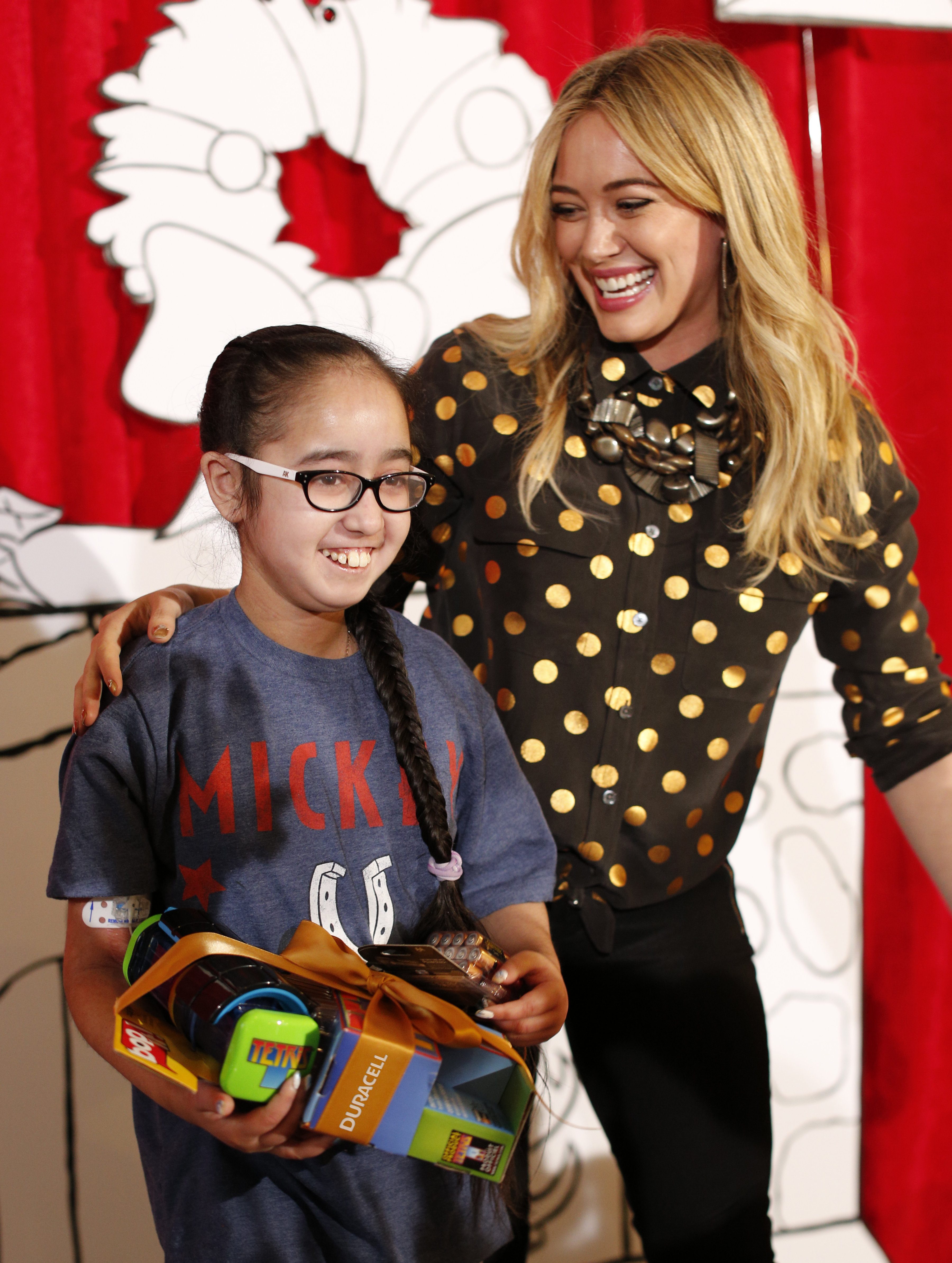 """Hilary Duff and SickKids patient ambassador, Avreen Sahota, launch the Duracell """"Powering Holiday Smiles"""" program, which will donate $1 to Children's Miracle Network for every pack of Duracell Quantum AA-16 batteries purchased by Dec. 27, 2013. (Photo: Business Wire)"""