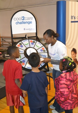 """Diandra Crawford (right) spins the prize wheel and shares healthy eating tips and recipes with Jackson-area kids participating in the Family Fun and Fitness Day hosted by UnitedHealthcare and Mississippi 4-H at the Mississippi Basketball and Athletics facility. The event was part of the UnitedHealthcare Mississippi 4-H """"Eat4-Health"""" partnership, which aims to reduce obesity rates among young people and families in the state through youth and community-based education and awareness programs. Photo by Kevin Bradnley"""