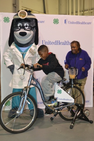 """Cheered on by Dr. Health E. Hound and Mississippi 4-H program leader Manola Erby, nine year old Joseph Walker pedals to create a healthy smoothie using a """"bike blender."""" The Family Fun and Fitness event was part of the UnitedHealthcare Mississippi 4-H """"Eat4-Health"""" partnership, which aims to reduce obesity rates among young people and families through youth and community-based education and awareness programs. The activities at the Family Fun & Fitness Day are part of a series of trainings and events made possible by a $30,000 grant provided by UnitedHealthcare to Alcorn State University Extension Program, which administers 4-H programs to all counties in the state. (Photo: Business Wire)"""