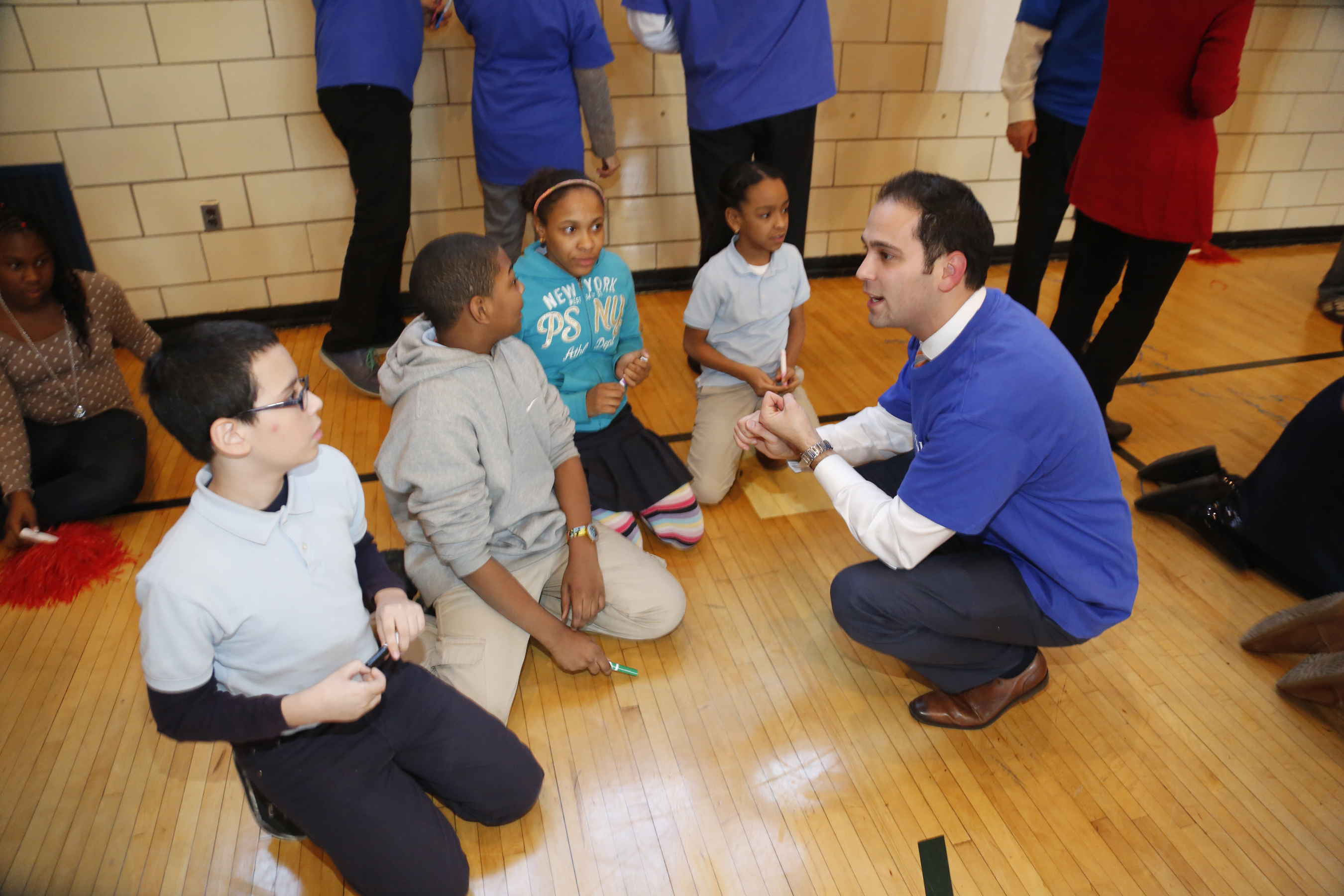 UnitedHealthcare's Victor Destefano meets with students from PS 15 as they prepare for a health trivia/physical fitness relay. The race was part of an event to kick off the second year of a collaboration between UnitedHealthcare and New York Giants Hakeem Nicks' nonprofit, Helping Hands. The organization provides backpacks of healthy foods and snacks for in-need children to take home over the weekends, when they may not otherwise have access to nutritious meals, through organizations like Blessings in a Backpack, which also joined in the afternoon's activities (Photo: Joe Rosen/PhotoBureau Inc.).