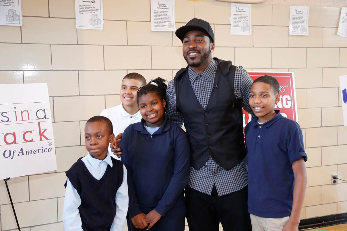New York Giants Hakeem Nicks with some of the more than 50 students from PS 15 who participated in an afternoon of health education and physical fitness to kick off the second year of a collaboration between UnitedHealthcare and Nicks' nonprofit, Helping Hands. The organization provides backpacks of healthy foods and snacks for in-need children to take home over the weekends, when they may not otherwise have access to nutritious meals, through organizations like Blessings in a Backpack, which also joined in the afternoon's activities (Photo: Joe Rosen/PhotoBureau Inc.).