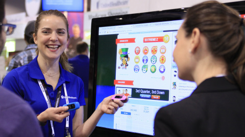 Arrianne Hoyland (left), game producer, UnitedHealthcare, explains to a CES attendee in Las Vegas how Zamzee's wearable activity meter monitors health and activity levels for kids. UnitedHealthcare announced at the 2014 International CES a new collaboration with Konami Digital Entertainment, Inc., and Zamzee to help reduce childhood obesity through school-based health programs. (Photo: Mike Keliher)