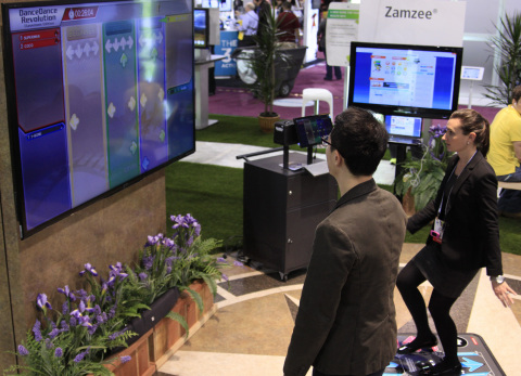 Robin Raskob (right), marketing manager at Zamzee and a CES attendee, demonstrate Zamzee's wearable activity meter on Konami's DanceDanceRevolution Classroom Edition. UnitedHealthcare announced at the 2014 International CES a new collaboration with Konami Digital Entertainment, Inc., and Zamzee to help reduce childhood obesity through school-based health programs. (Photo: Mike Keliher)