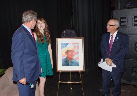 President George W. Bush accepts a portrait from Morgan Davidson, a 21-year-old illustration major at Ringling College of Art and Design in Sarasota after his Jan. 14 talk at the Ringling College Library Association Town Hall Lecture Series. A native of Florida, Davidson became interested in drawing at an early age, and enrolled at Ringling, where she has focused on portraits, fashion and nature. After graduation in May, Davidson plans to become a freelance artist, helping clients bring their creative ideas to life. Jay Logan, Town Hall Chairman, on right. (Photo credit: Robert Pope)