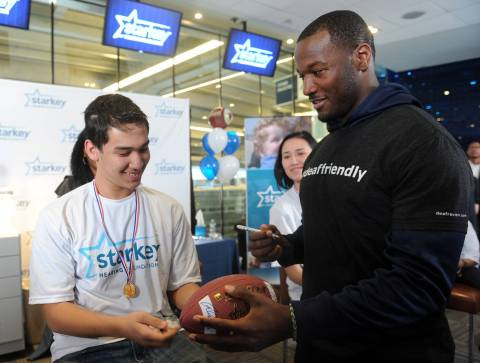 IMAGE DISTRIBUTED FOR STARKEY HEARING FOUNDATION - Seattle Seahawk Derrick Coleman, the first legally deaf offensive player in the NFL, signs a football for Joseph Pon,15, of Queens, NY, after he received free hearing aids at the Starkey Hearing Foundation's mission, Saturday, Feb. 1, 2014, at Yankee Stadium in New York. (Photo by Diane Bondareff/Invision for Starkey Hearing Foundation/AP Images)
