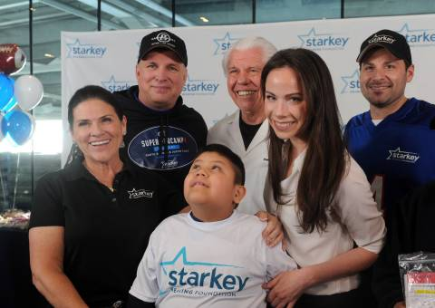 IMAGE DISTRIBUTED FOR STARKEY HEARING FOUNDATION - Tani Austin, left, co-founder Starkey Hearing Foundation, Garth Brooks, second left, Bill Austin, center, Founder of Starkey Hearing Foundation, Barbara Bush, second right, and Steven Sawalich, Senior Executive Director, Starkey Hearing Foundation, pose with William Romero, 7, of Brooklyn, after he received free hearing aids at the Foundation's hearing mission, Saturday, Feb. 1, 2014, at Yankee Stadium in New York. (Photo by Diane Bondareff/Invision for Starkey Hearing Foundation/AP Images)