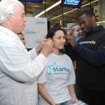 IMAGE DISTRIBUTED FOR STARKEY HEARING FOUNDATION - Seattle Seahawk Derrick Coleman, right, the first legally deaf offensive player in the NFL, and Bill Austin, Founder of Starkey Hearing Foundation, fit Victoria Pon,16, of Queens, NY, with free hearing aids at the Foundation's hearing mission, Saturday, Feb. 1, 2014, at Yankee Stadium in New York. (Photo by Diane Bondareff/Invision for Starkey Hearing Foundation/AP Images)