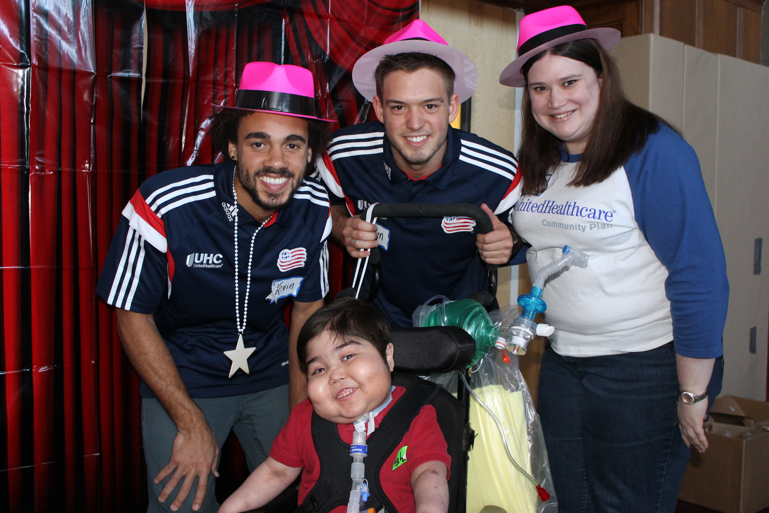 New England Revolution defender Kevin Alston and midfielder Kelyn Rowe pictured with patient of Franciscan Hospital for Children and Cynthia Mailhiot of UnitedHealthcare (Photo: Project Sunshine).