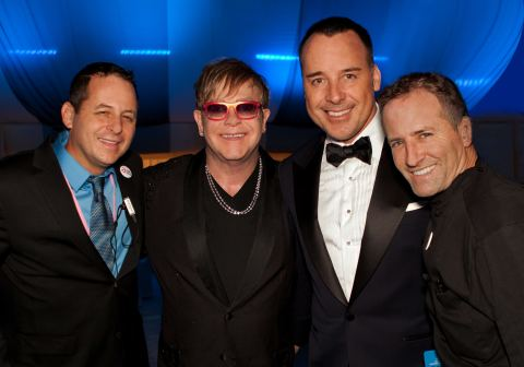 Flanked (l-r) by Crumble Catering's Chris Diamond and Chef Wayne Elias are Sir Elton John and partner David Furnish. From its humble beginnings in 1992, the Elton John AIDS Foundation gala has raised more than $300 million worldwide over the past two decades. (Photo: Business Wire)