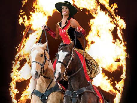 Extraordinary Roman rider Dusti Crain leaps through the ring of fire during Dixie Stampede's 27th season in Pigeon Forge, Tennessee. (Photo: Business Wire)