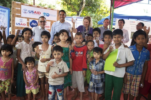 USAID Administrator Rajiv Shah (center) joins children from North Okkalapa Township, outside Burma's capital Rangoon on Feb. 27, 2014 to launch a health training program and demonstrate the use of Procter and Gamble's water purifying sachets. In Burma, USAID and P&G partner to provide clean drinking water and promote sanitation practices for some of the country's most vulnerable. (Photo: Business Wire)