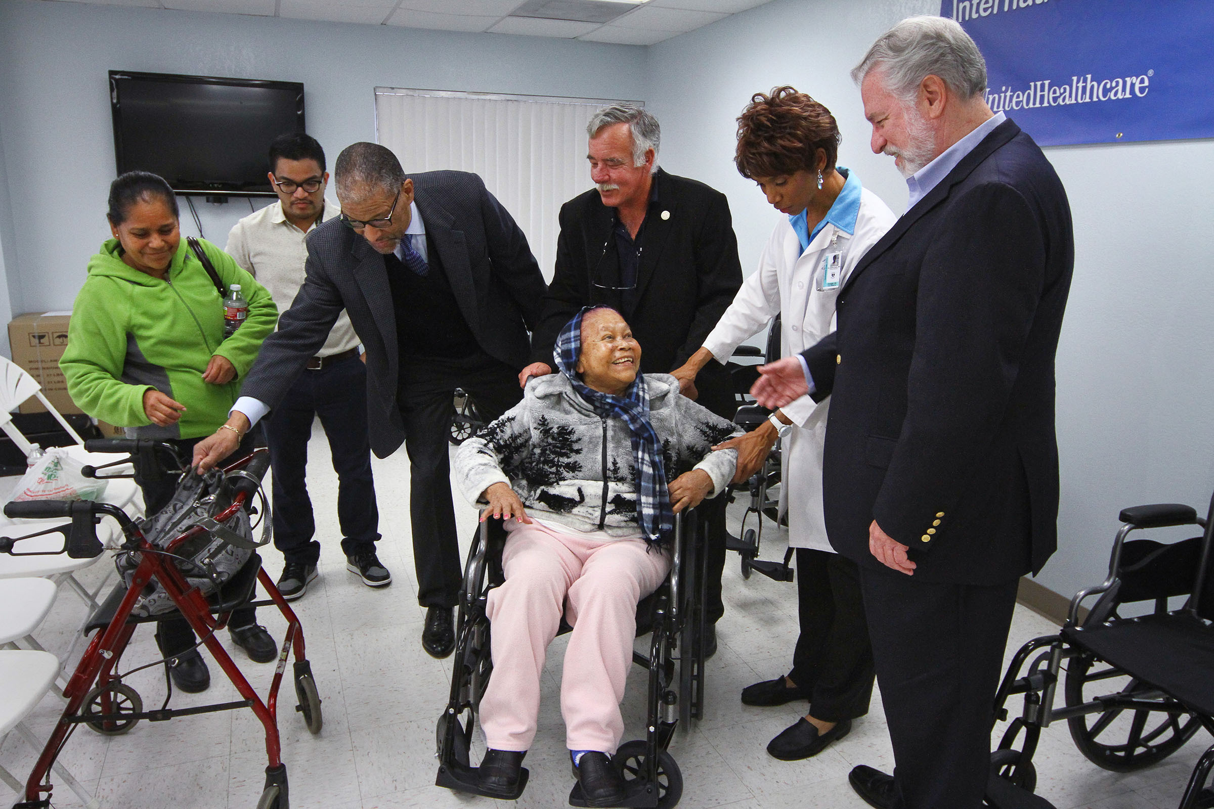 Antonia Palacios (sitting), of Santa Ana receives a wheelchair on Friday, Feb. 28 at Lestonnac Free Clinic. Looking on from left to right: Maria Chamu, daughter of Palacios; Bryan Melgar, Lestonnac staff member; Keith Emmons, M.D., market medical director, UnitedHealthcare; Ed Gerber, executive director of Lestonnac; Andrea Avery, M.D., Lestonnac board member and volunteer physician; and Russ Bennett, vice president, Latino Health Solutions, UnitedHealthcare (Photo: Jamie Rector).
