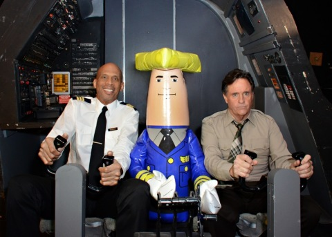 """""""Roger Murdock"""" (Kareem Abdul-Jabbar), """"Ted Striker"""" (Robert Hays) and Otto Pilot in the original """"Airplane!"""" cockpit during the shoot of the new aerial ads for the Wisconsin Department of Tourism. The ads premiered today at WIGCOT. (Photo: Business Wire)"""