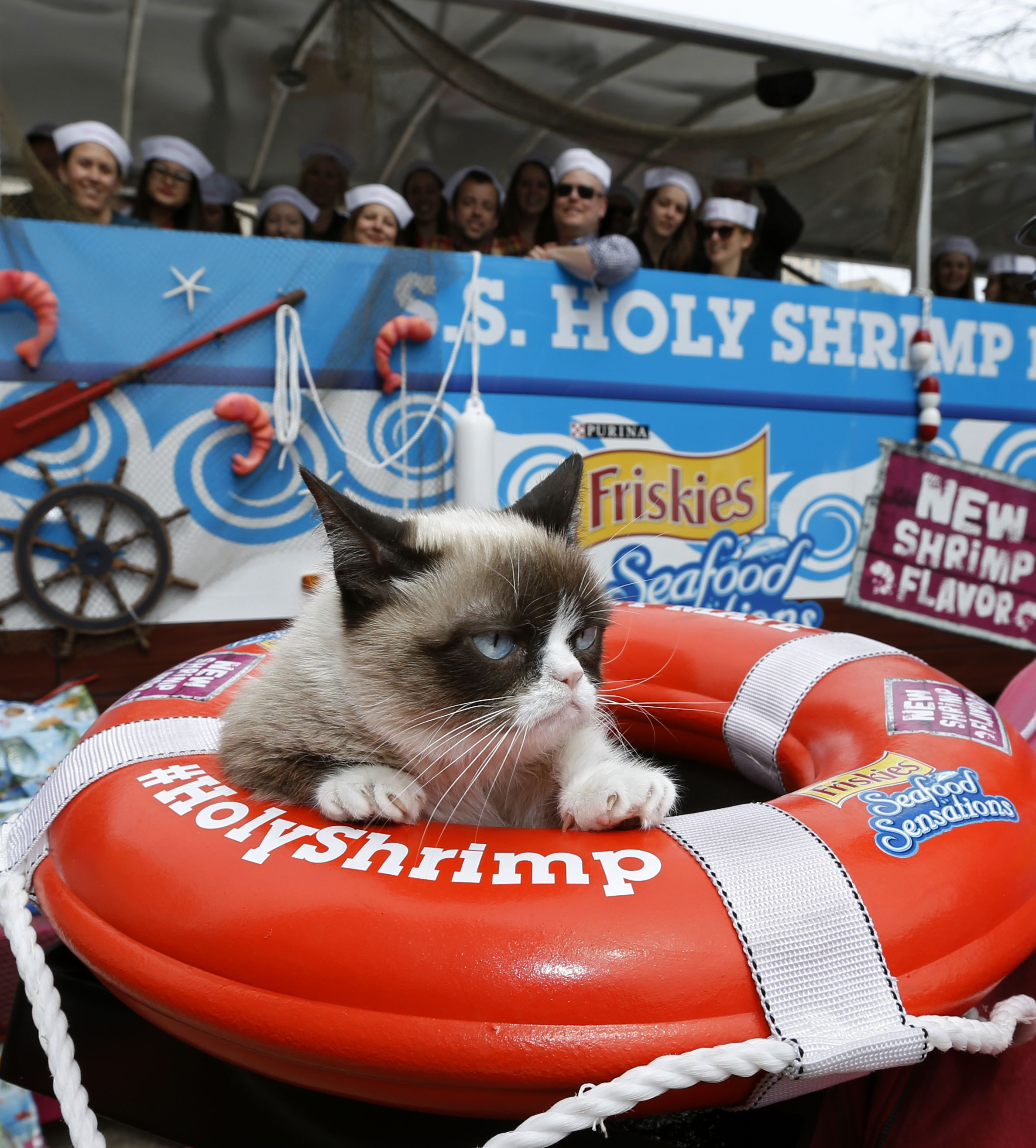 """Passengers join Grumpy Cat, the """"Worst Mate,"""" of the Friskies' S.S. Holy Shrimp Boat as it embarks on its maiden voyage during the Austin-based festival on Friday, March 7, 2014. The ship, designed by Friskies to promote the NEW shrimp flavor in Seafood Sensations cat food, delivered Grumpy Cat in style to the Mashable House for a sea-faring themed photo booth appearance. (Erich Schlegel/AP Images for Friskies)"""