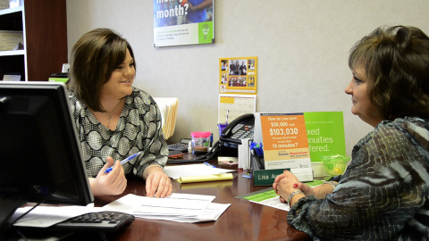 Lisa Austin, left, Regions Bank branch manager in Hot Springs, Ark., speaks with colleague Kathy Jac ...